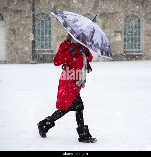 Eine Frau zu Fuß durch den Schnee in Victoria Square, Birmingham, UK. Der Schirm zeigt den Houses of Parliament Stockbild