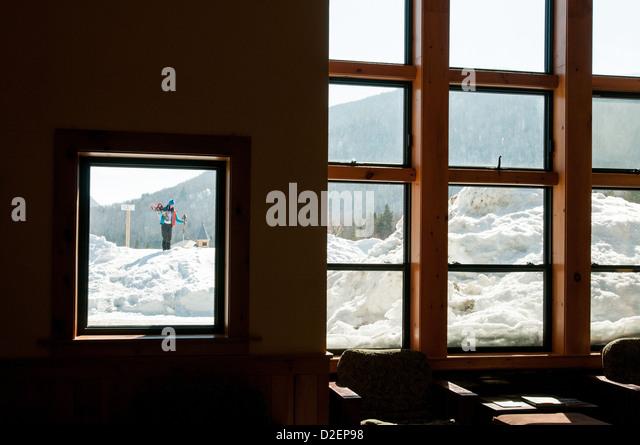 Frau vor der Tür einer Lodge mit Schneeschuhen und viel Schnee. Stockbild