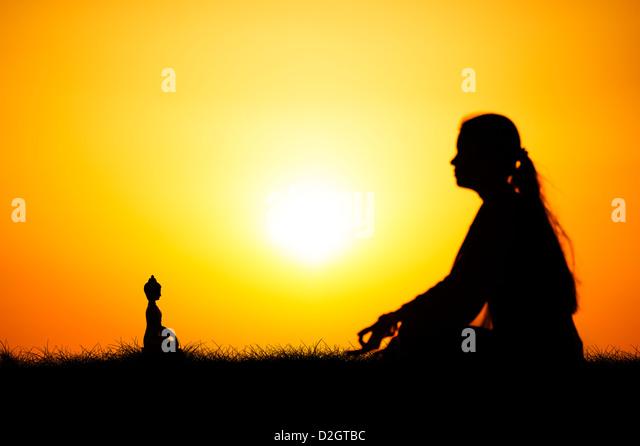 Sonnenuntergang Silhouette eines indischen Mädchen meditieren vor Buddha-Statue. Andhra Pradesh, Indien Stockbild