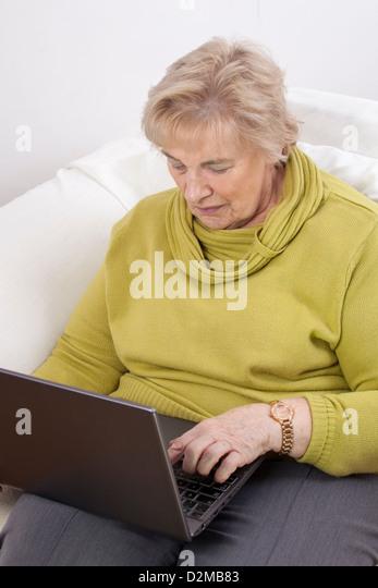 Reife Dame mit einem Laptop. Stockbild