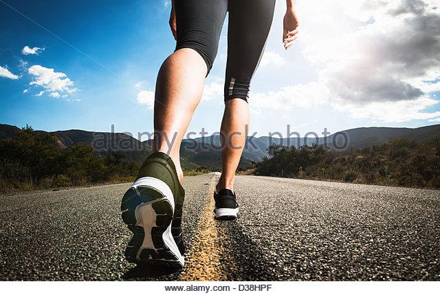 Frau läuft auf Landstraße Stockbild