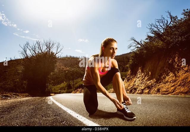 Läufer, die Schnürung der Schuhe auf Landstraße Stockbild