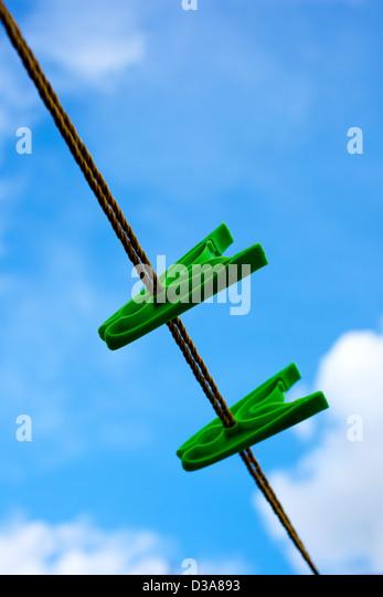 Zwei grüne Pflock auf einer Wäscheleine vor einem bewölkten blauen Himmel. Stockbild