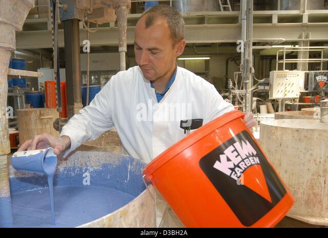 (Dpa) - Arne Breu nimmt eine Probe von blauer Farbe beim Lacke Hersteller Keim Farben in Diedorf, Deutschland, 16. Stockbild