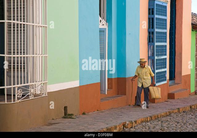 Alten kubanischen Mann zu Fuß entlang Pastell farbigen Häuser mit Barrotes und Gitter in Trinidad, Kuba Stockbild