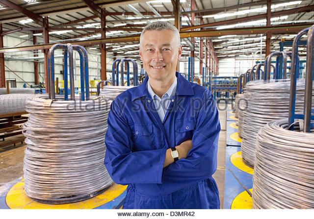 Porträt der lächelnde Arbeiter in Overalls stehen unter Spiralkabel im Lager Stockbild