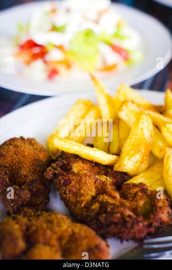 ölige gebratene Nahrung, ungesunde Lebensmittel. überfrittiert Huhn mit Pommes Frites. Abgeschlossen mit Stockbild