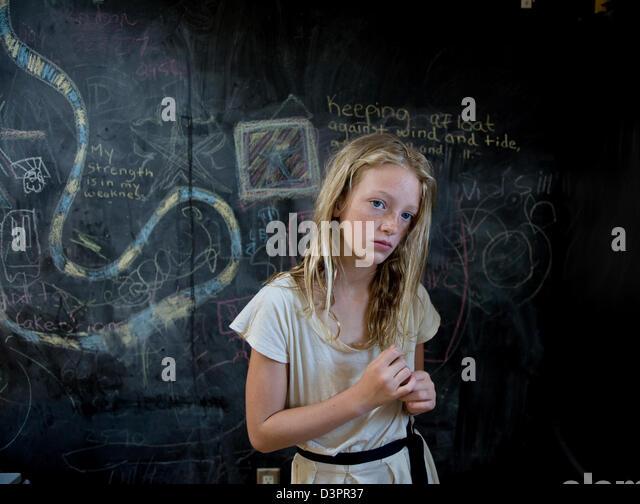 Blonde Mädchen vor einer Tafel Stockbild