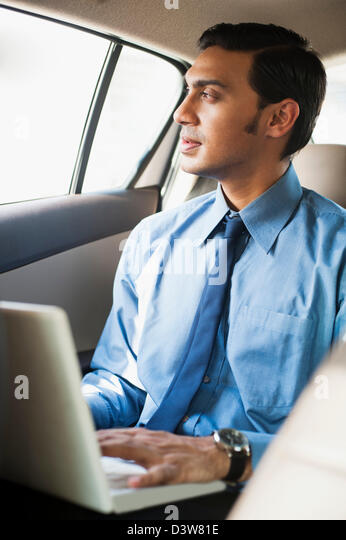 Bengali Geschäftsmann mit einem Laptop in ein Auto Stockbild