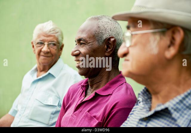 drei alte Männer sitzen auf der Bank im Park und im Gespräch Stockbild