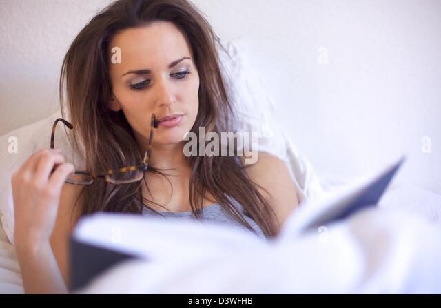 Brünette Frau vertieft in ein Buch in ihrem Zimmer Stockbild
