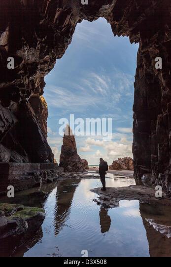 Nadel rock mit stehenden Person in plemont Höhle, Jersey, Channel Islands, Großbritannien Stockbild