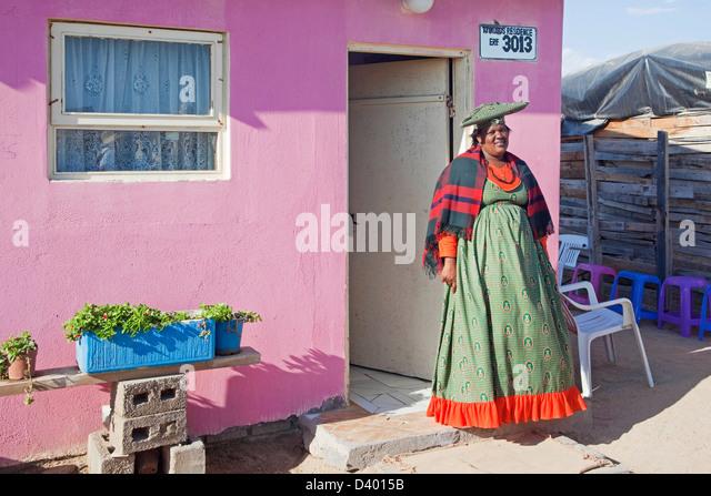Herero-Frau in bunten Trachten vor ihrem Haus in der Gemeinde in der Nähe von Swakopmund, Namibia, Südafrika Stockbild