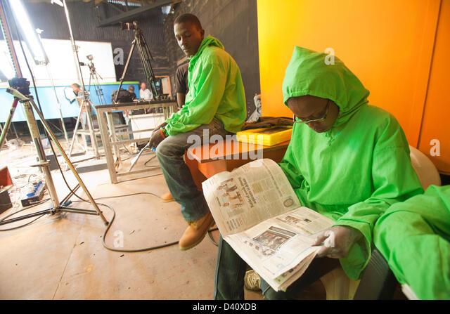 Nairobi, Kenia. 26. Februar 2013. Puppenspieler in Greenscreen Outfit eine Pause und liest eine Zeitung zwischen Stockbild