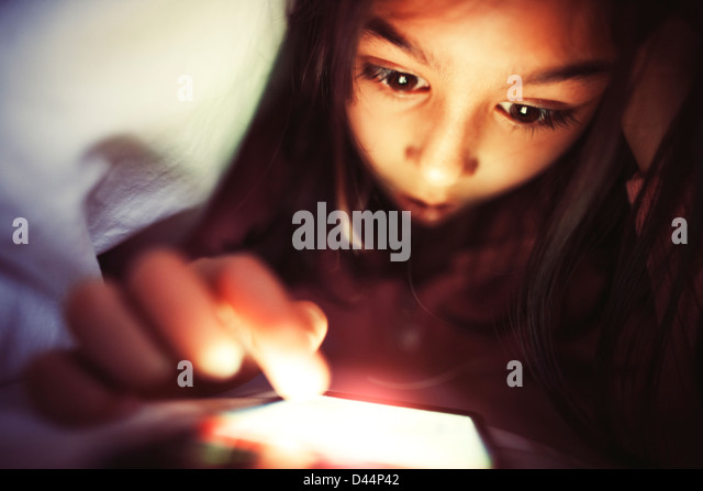 Mädchen nutzt Smartphones unter Bettdecken Stockbild