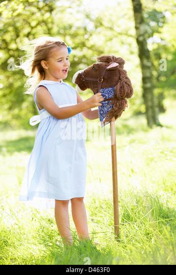 Junge Mädchen spielen mit Steckenpferd In Sommerwiese Stockbild