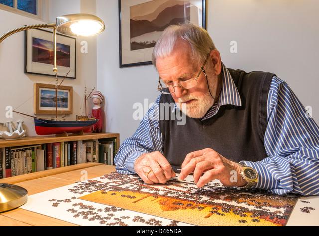 Pensionierter Mann, Rentner, mit Puzzle zu Hause. UK Stockbild
