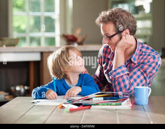 Vater und Sohn, die Hausaufgaben am Küchentisch Stockbild