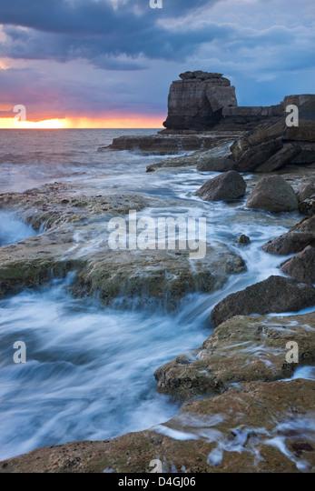 Wellen gegen die felsige Küste der Portland Bill bei Sonnenuntergang. Isle of Portland, Dorset, England. Frühling Stockbild