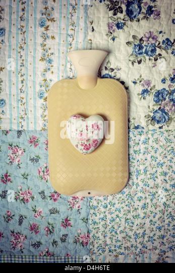 eine Wärmflasche auf einem Vintage Bett mit einem floralen Herzen Stockbild