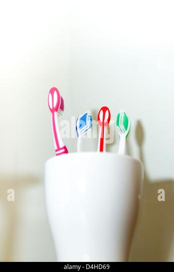 Vier verschiedene farbige Zahnbürsten in weiße Tasse Stockbild