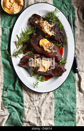 Gegrilltes Steak Denver, garniert mit Sardellen Butter über Rosmarin Zweige auf einem weißen Teller auf Stockbild