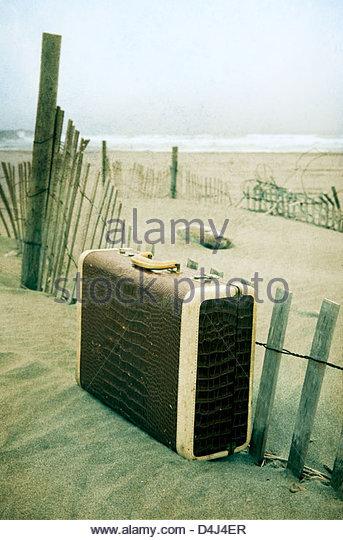 Alte Leder strukturierte Koffer aufgegeben am Strand im sand Stockbild