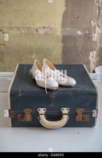 Schuhe, die sitzen auf antike Koffer Stockbild