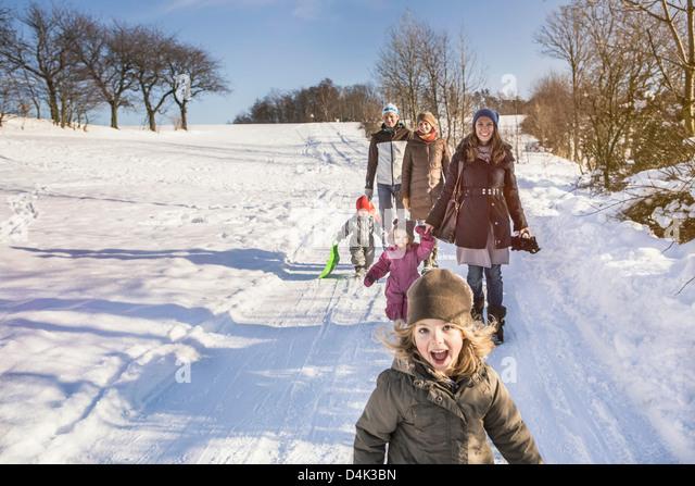 Familie gehen zusammen im Schnee Stockbild