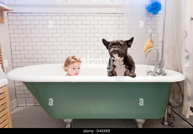 Mädchen sitzen mit Bulldogge in Badewanne Stockbild
