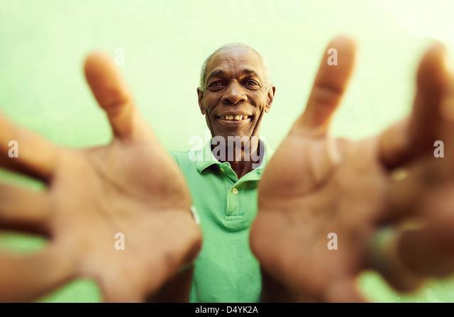 Porträt von senior schwarzer Mann mit Händen und Armen zu öffnen auf Kamera zeigen. Grüner Hintergrund Stockbild