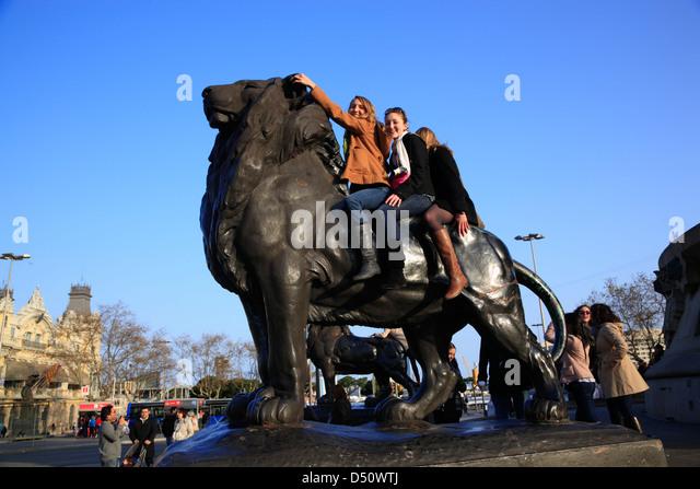 Junge Menschen auf einem Löwen am Plaça Portal De La Pau am Hafen, Barcelona, Spanien Stockbild