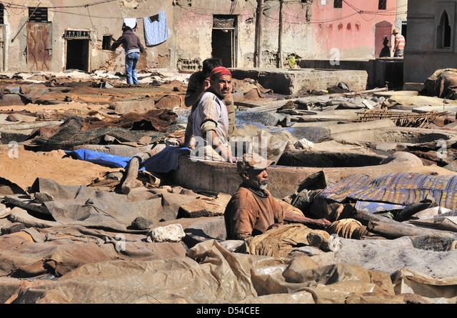 Männer tendenziell die Kuh versteckt einweichen in Wasser in die Tanks in den Gerbereien in Marrakesch, Marokko Stockbild