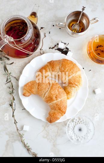 Croissants, Honig und Tee auf Tisch Stockbild