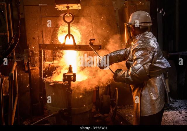 Arbeiter gießt geschmolzenes Metall in Gießerei Stockbild