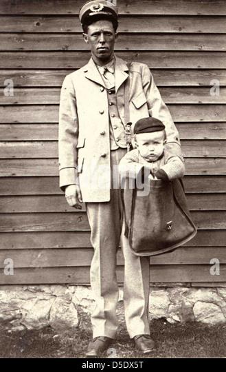 Uniformierte Briefträger mit Kind im Briefkasten Stockbild