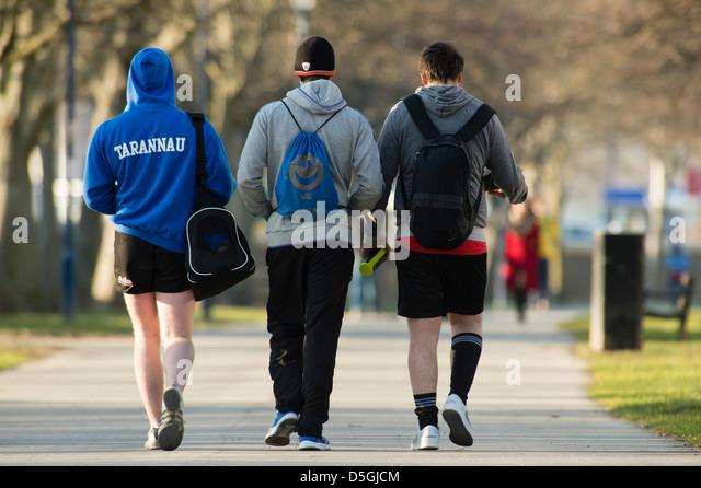 Rückansicht von drei jungen Männern mit Kit Taschen auf dem Rücken zu Fuß, oder aus einem Sporttraining Stockbild