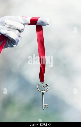 eine Hand in weißen Handschuhen hält einen alten Schlüssel auf einem roten Band Stockbild