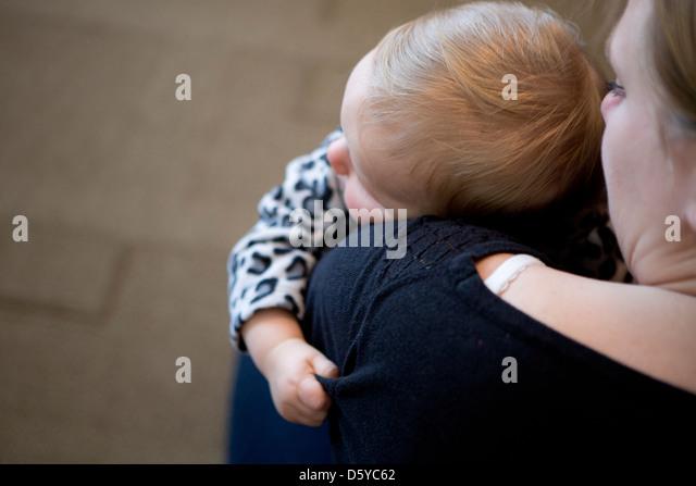 Babymädchen auf Mutters Schulter Stockbild