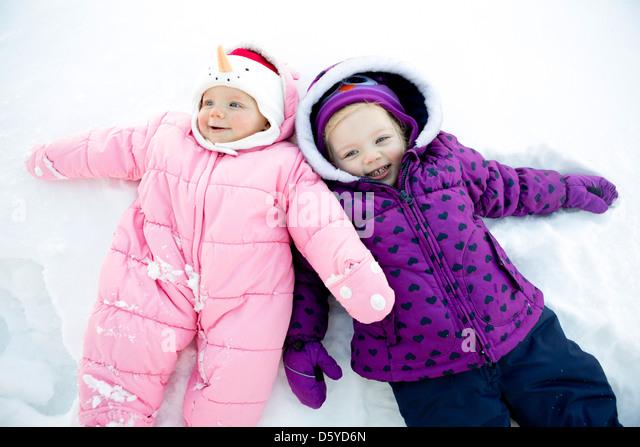 Mädchen mit Baby Schwester liegend im Schnee Stockbild