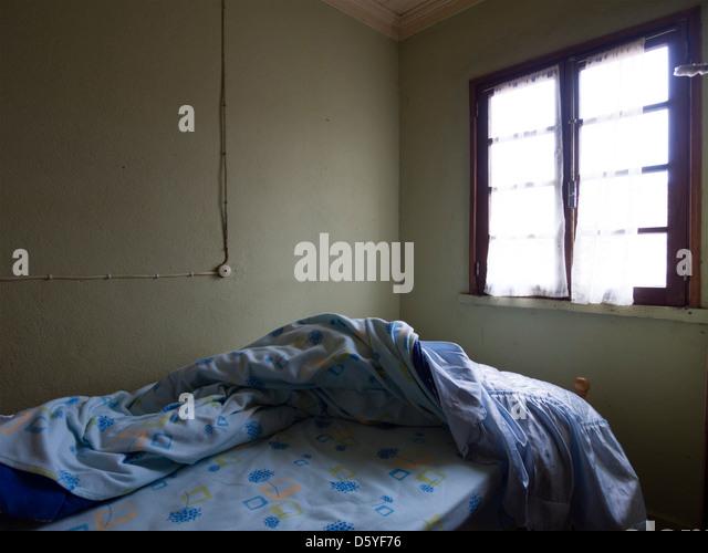 Ungemachten Bett in einem dunklen Schlafzimmer Stockbild