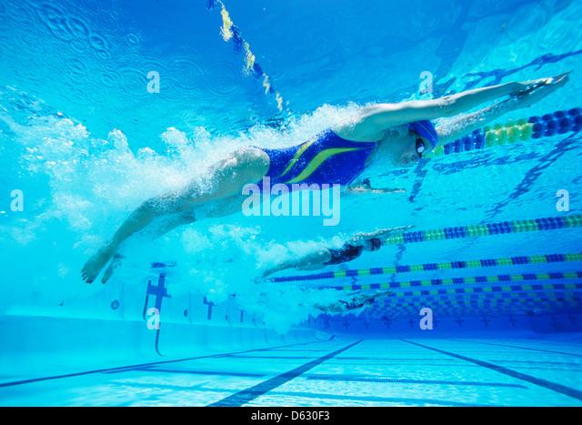 Junge weibliche professionelle Teilnehmer racing im pool Stockbild
