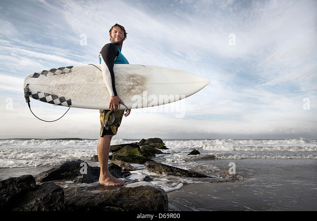 Surfer, die auf Felsen am Strand Stockbild