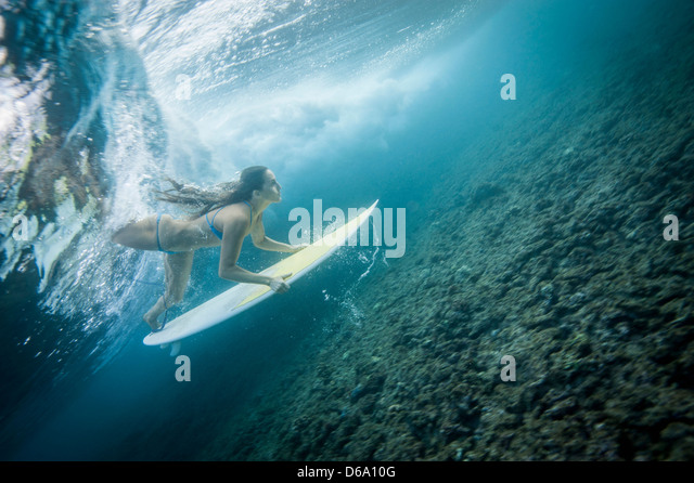 Surfer unter Welle in Wasser tauchen Stockbild
