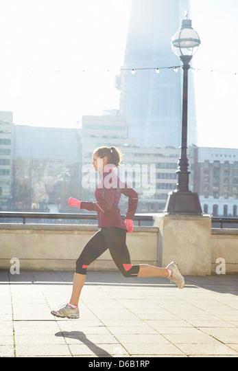 Frau läuft auf städtische Brücke Stockbild