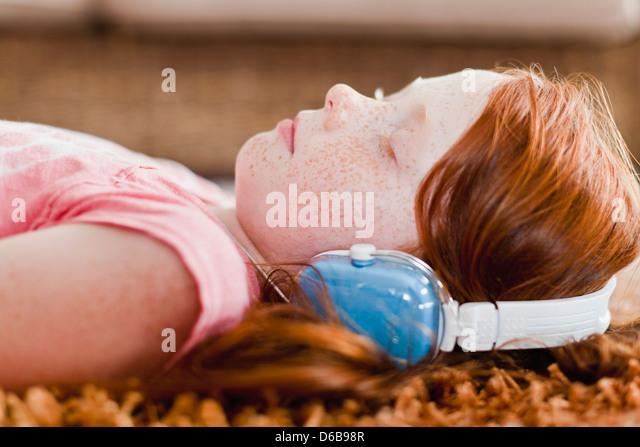 Mädchen hören Kopfhörer auf Teppich Stockbild