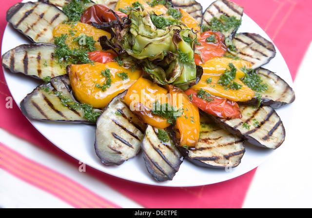 Gebratene Aubergine, Paprika und Zucchini mit einem Sommer-Kräuterdressing. Stockbild