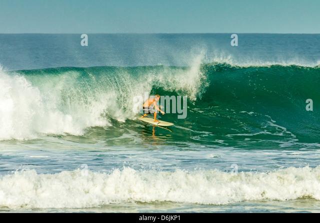 Surfer auf einer Welle an beliebten Playa Guiones surf Strand, Nosara, Nicoya Halbinsel, Provinz Guanacaste, Costa Stockbild
