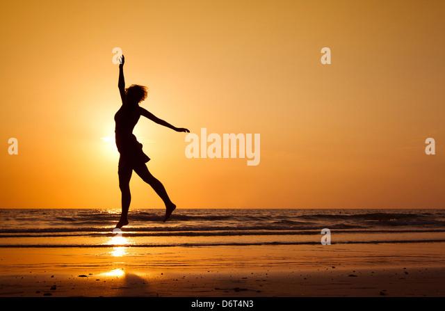 Silhouette der glückliche Frau springen am Strand, gesunde Lebensweise Stockbild