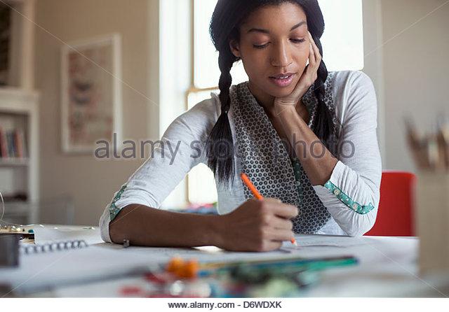 Mitte Erwachsenen weiblichen Schmuck Künstler Zeichnung am Schreibtisch Stockbild